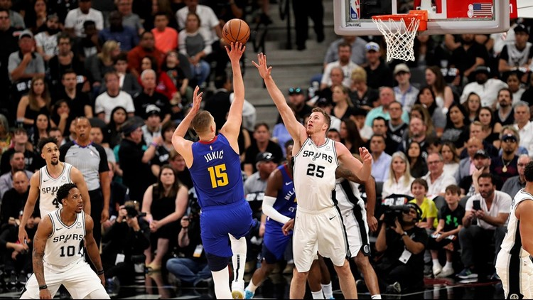 BKN Nuggets center Nikola Jokic, shooting over Spurs center Jakob Poeltl