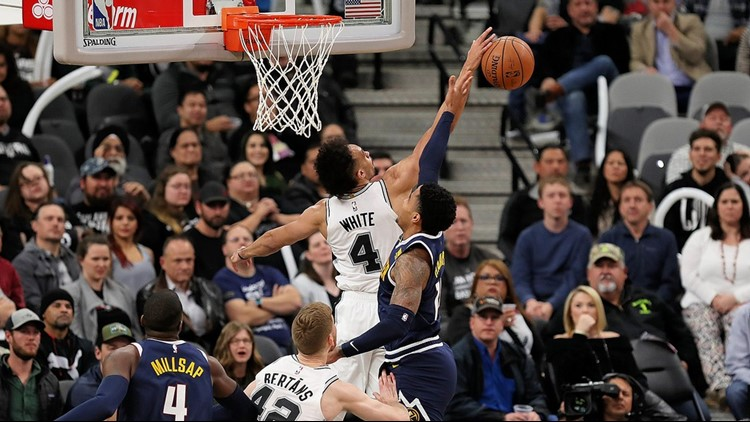 Spurs point guard Derrick White blocks a shot in the game against the Nuggets