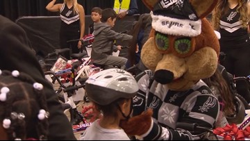 Local kids receive gifts of bikes and helmets at Spurs game