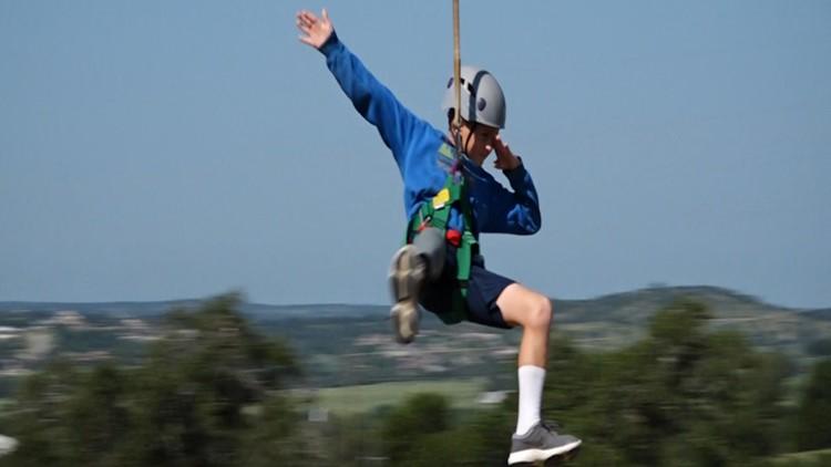 Camper shows off his dab while ziplining at Camp David