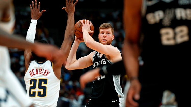 Spurs forward Davis Bertans keeps the ball away from Nuggets guard Malik Beasley in Game 2