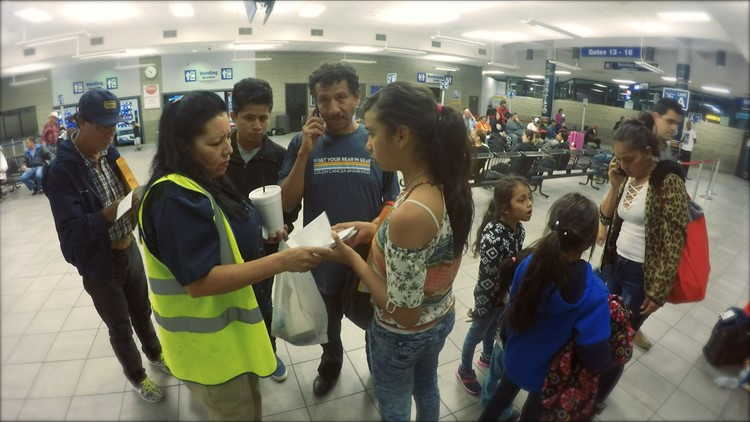 Migrants released by immigration authorities ask for help with their tickets at Houston bus station