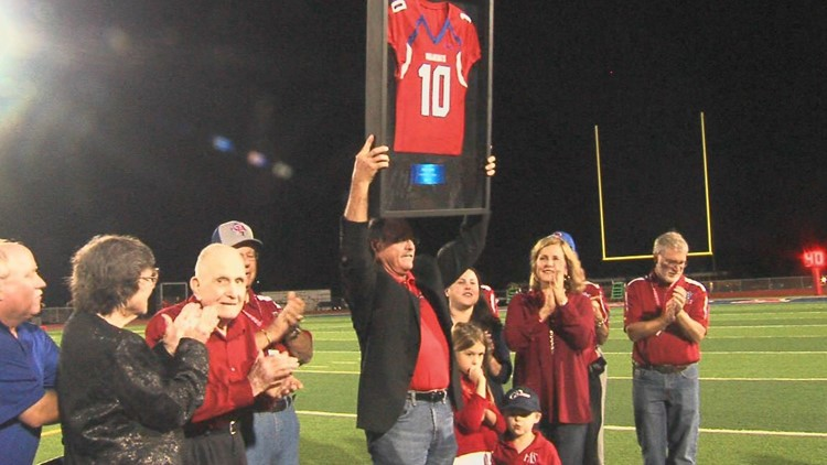 Former Gregory-Portland football coach Ray Akins, third from left, claps as his son, Marty, who played quarterback for him, raises his framed retired jersey No. 10 at a G-P game this season.
